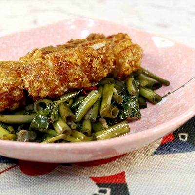 Crispy roast pork belly on a bed of sauteed swamp spinach