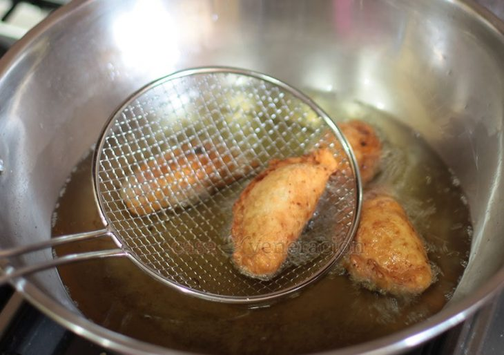 Scooping out fried empanada from hot oil