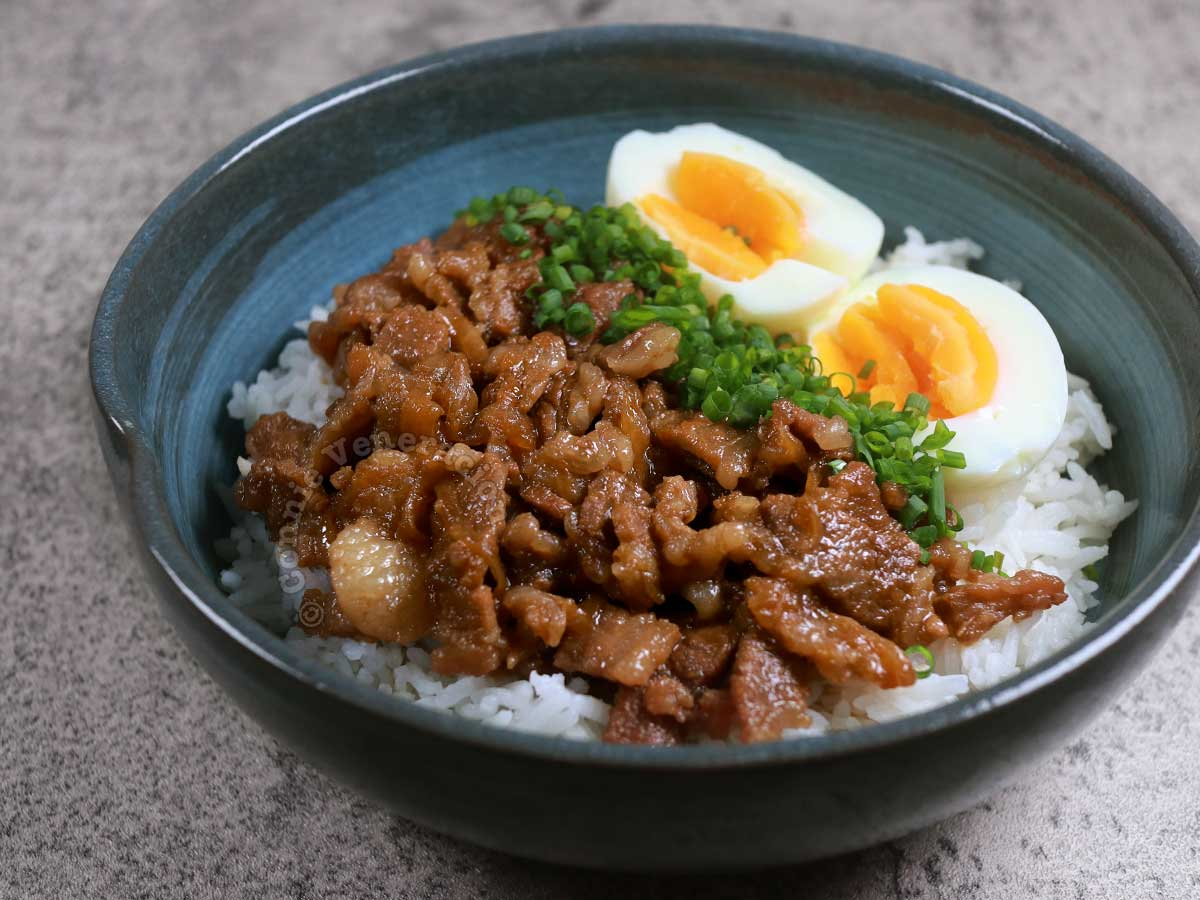 Gyudon with egg halves and scallions in blue bowl