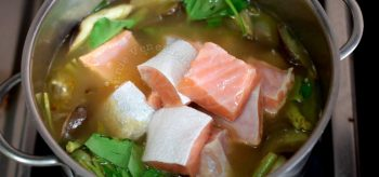 Adding salmon belly to vegetables in pot to cook sinigang