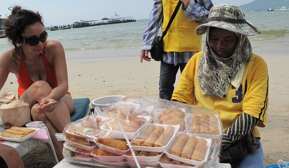 A hawker selling fried spring rolls and chicken at Patong Beach, Phuket, Thailand