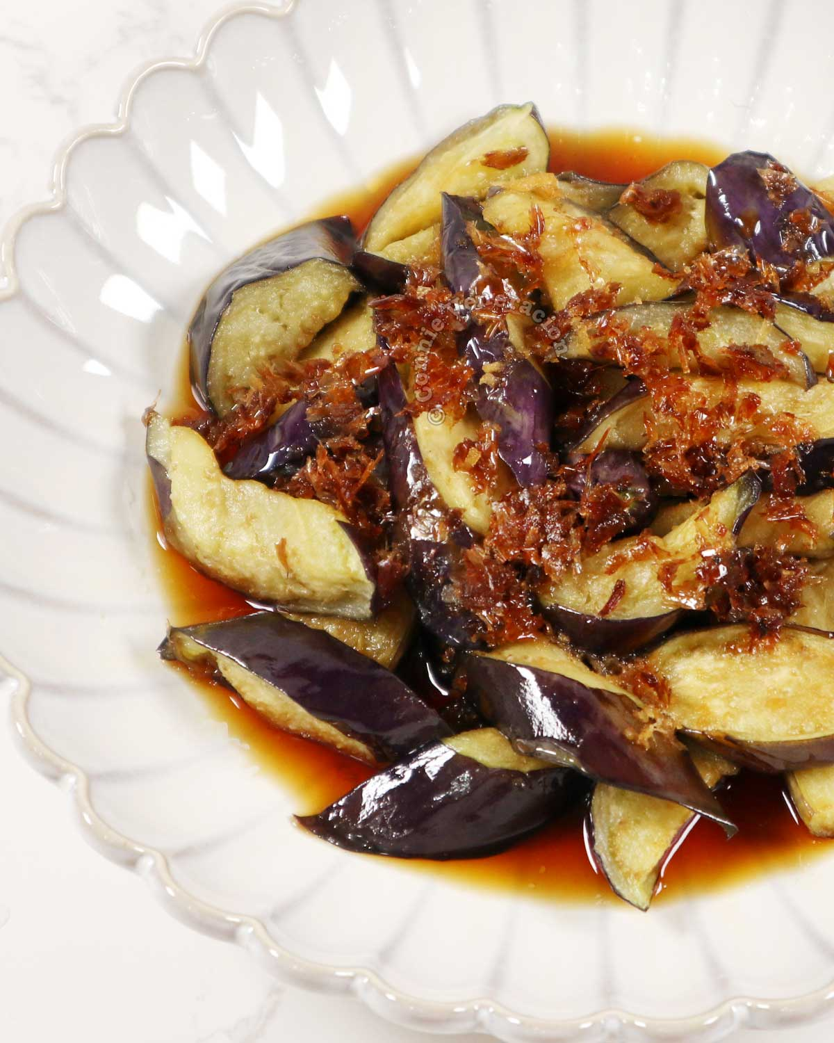 Japanese fried eggplants with ginger dashi sauce and bonito flakes in white bowl