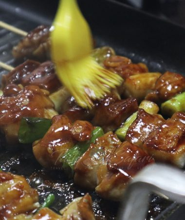 Cooking yakitori: brushing skewered chicken with tare sauce
