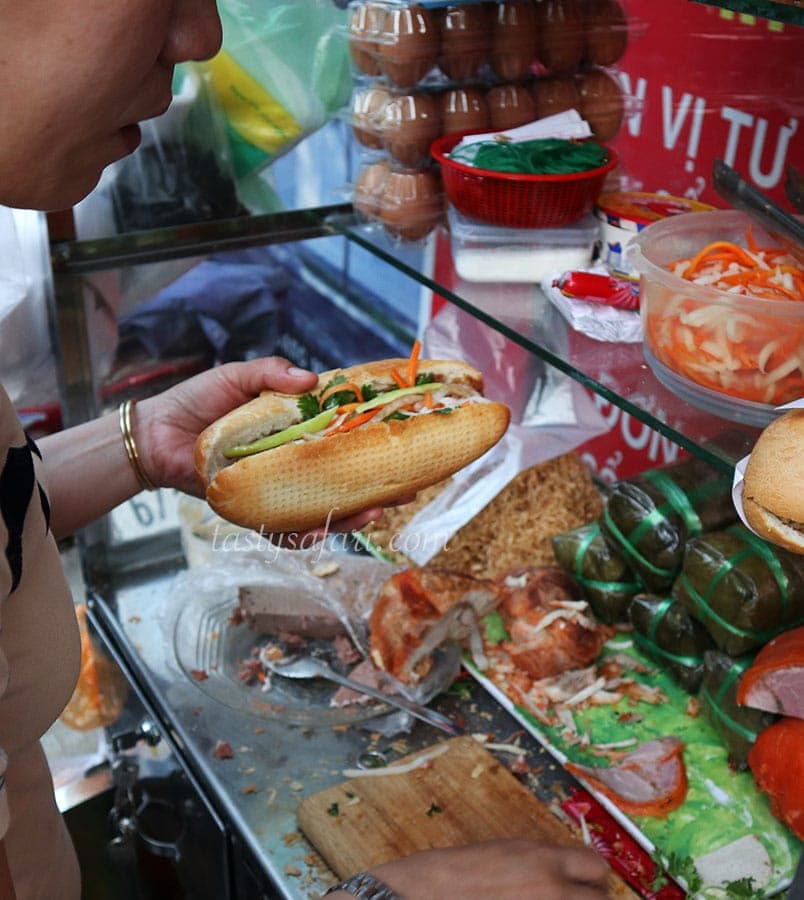 A banh mi vendor adding vegetables to the filling