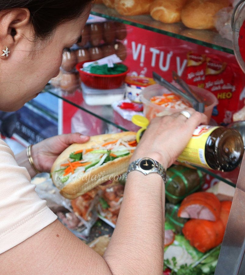 A banh mi vendor drizzling sauce over the filling