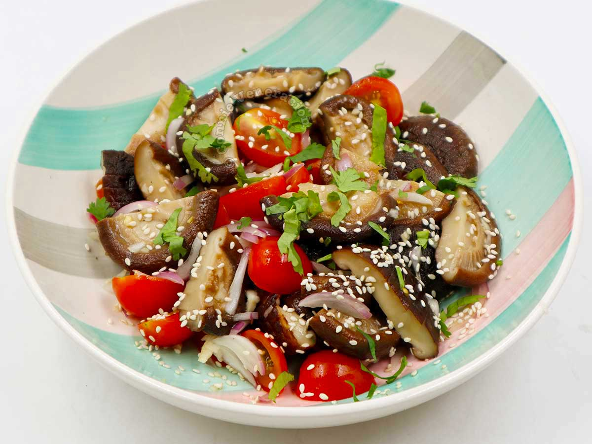Shiitake and cherry tomato salad garnished with toasted sesame seeds and cilantro