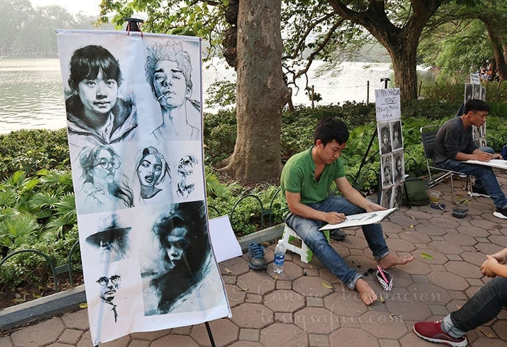 Artists offer to draw your portrait. Hoan Kiem Lake, Hanoi.