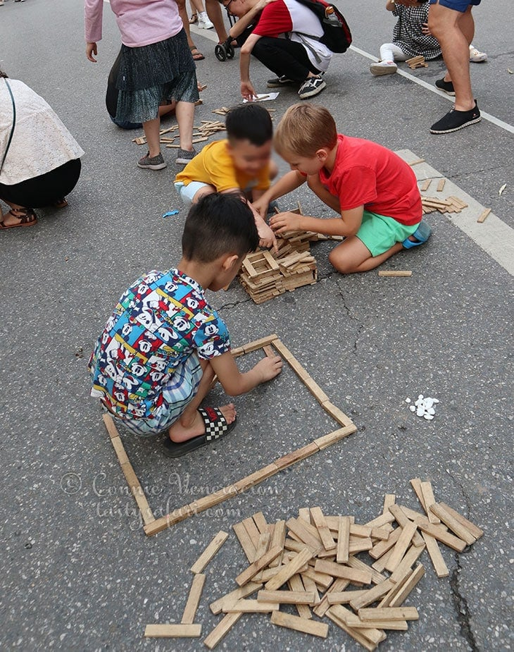 Young boys playing with wood sticks. Hoan Kiem Lake, Hanoi