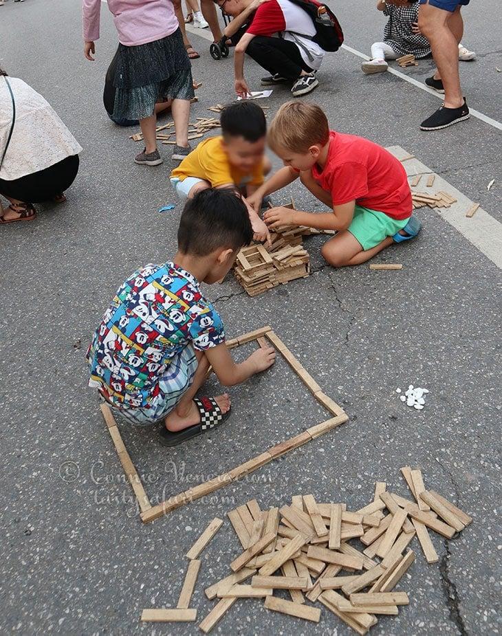 Young boys playing with wood sticks. Hoan Kiem Lake, Hanoi