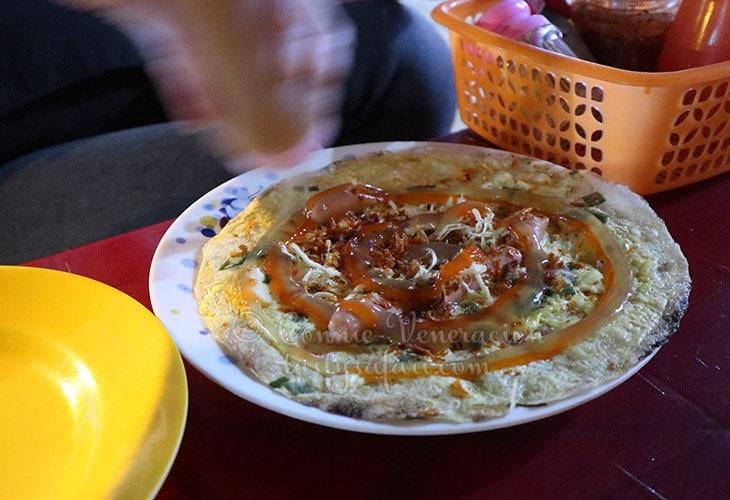 Sprinkling crispy spices over Vietnamese pizza