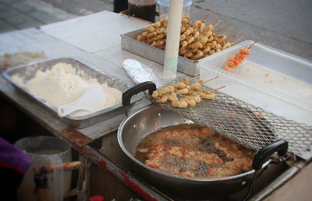 Skewered and battered chicken intestines are deep fried by a street vendor. Antipolo City, the Philippines.