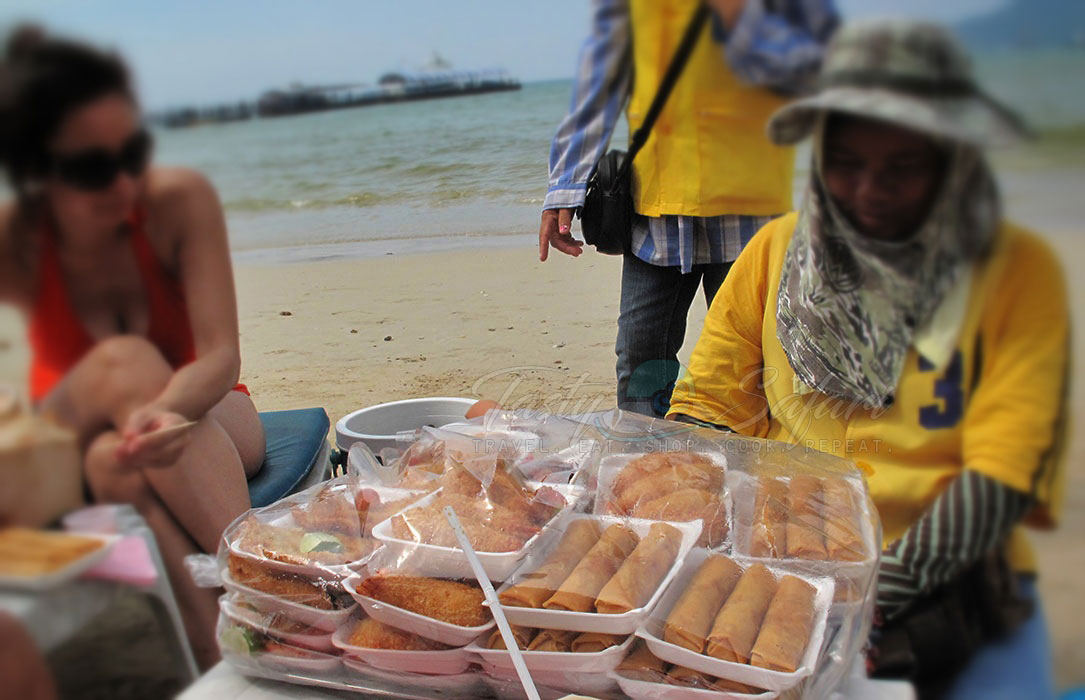 A hawker selling fried spring rolls and grilled chicken. Patong Beach, Phuket, Thailand