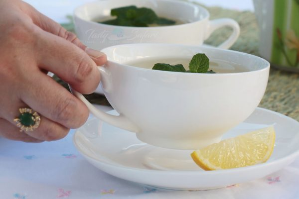 Hot tea with mint leaves and wedge of lemon