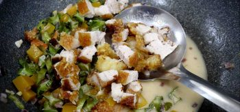 Adding crispy pork belly to mixed vegetables in coconut cream