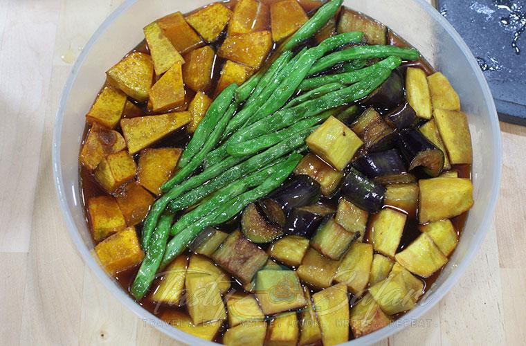Green beans, squash, sweet potatoes and eggplants soaking in sauce to make mixed vegetables agebitashi
