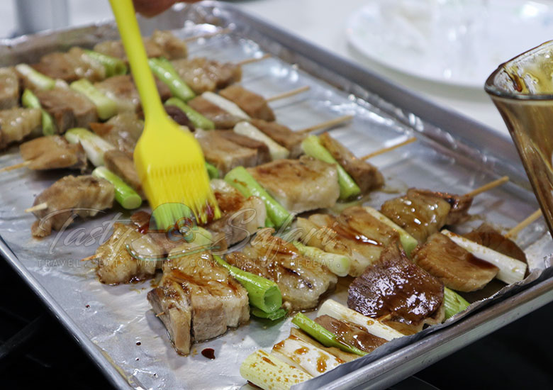 Brushing skewered pork and green onion with glaze to make yakiton or Japanese grilled skewered pork