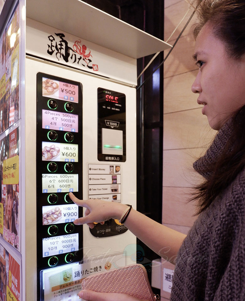 Ordering takoyaki at a food stall in Dotonbori using a ticket machine