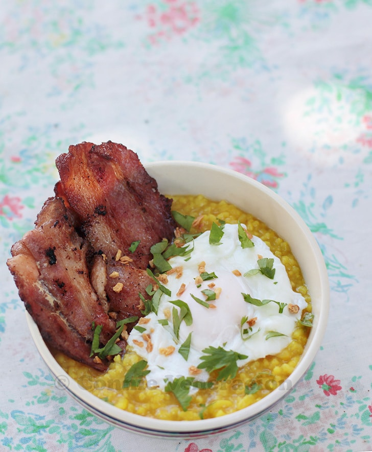 Turmeric-flavored congee with poached egg and bacon strips
