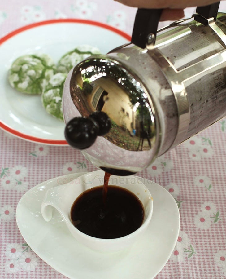 Pouring hot coffee from a French press