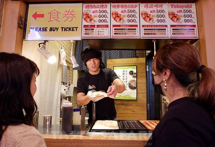 Ordering takoyaki in Dotonbori
