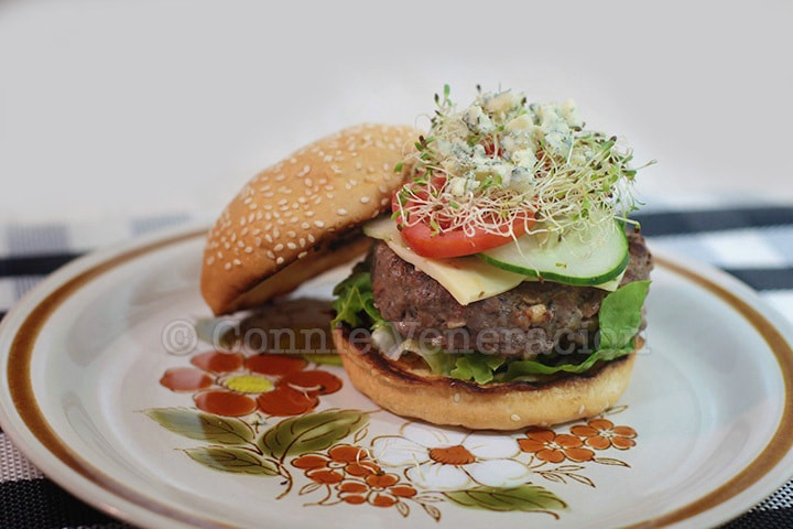 Burger topped with cheese, cucumber, tomato, alfalfa sprouts and blue cheese