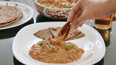 Dipping paratha in butter chicken sauce