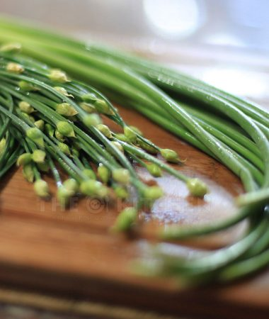 Chinese chives and garlic scapes on a bamboo chopping board