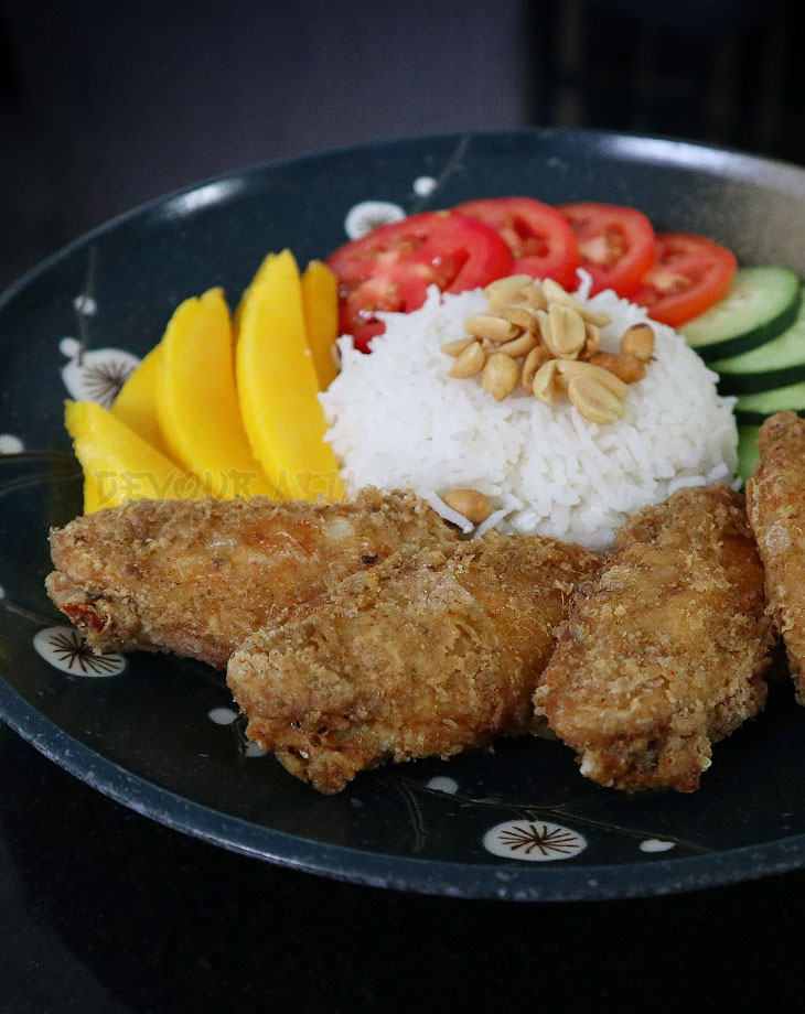 A plate of nasi lemak (rice cooked in coconut milk) with fried chicken wings, tomatoes, cucumber, mango and peanuts