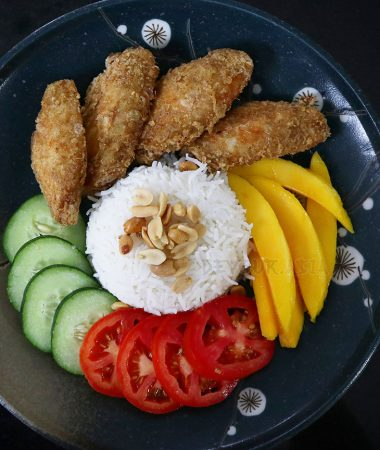 Nasi lemak (rice cooked in coconut milk) with fried chicken wings, tomatoes, cucumber, mango and peanuts