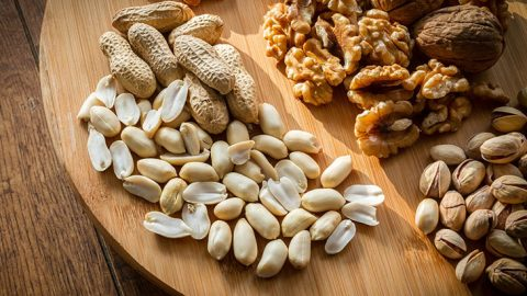 Assorted nuts on wooden board