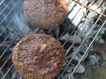 Burgers cooking on a charcoal grill