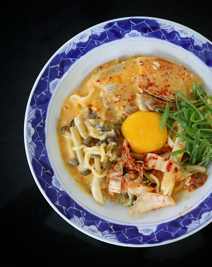 Ramen, pork, kimchi egg and cheese in a bowl