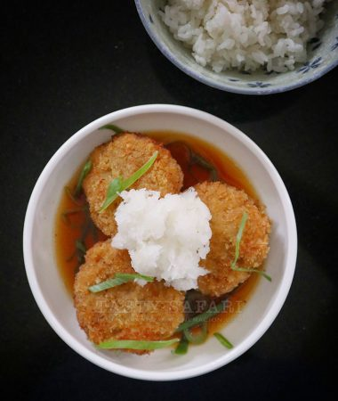 Hambagu (Japanese burger steaks) in dashi sauce topped with grated radish and served with rice on the side