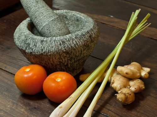 Tomatoes, lemongrass and ginger with mortar and pestle