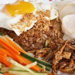 Nasi goreng (indonesian fried rice) with egg, carrot, cucumber, dilis and krupuk