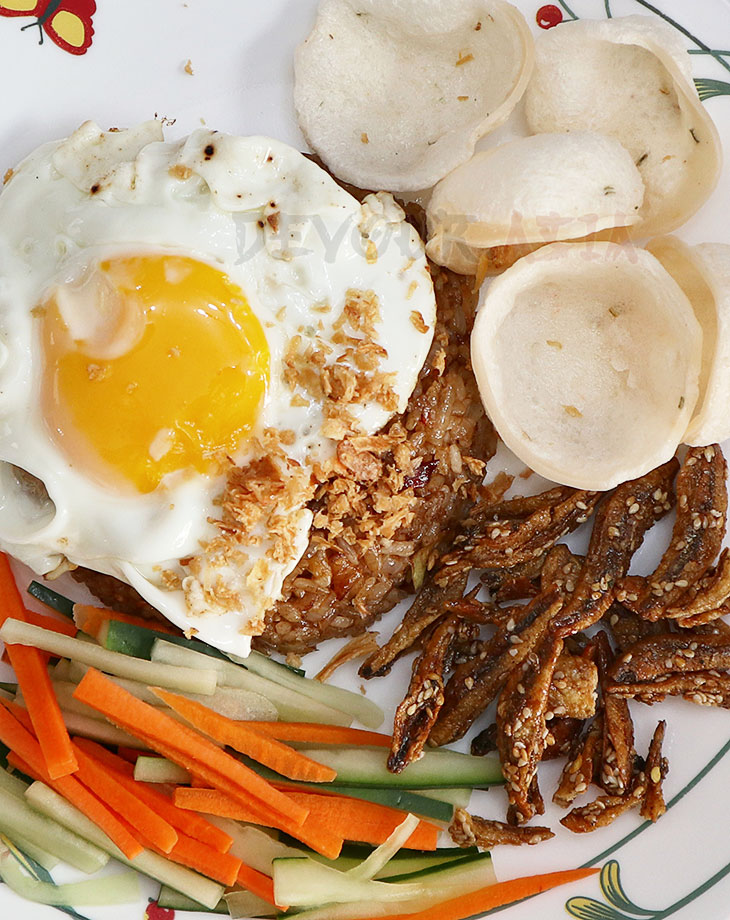 A plate of nasi goreng (indonesian fried rice) with egg, carrot, cucumber, dilis and krupuk