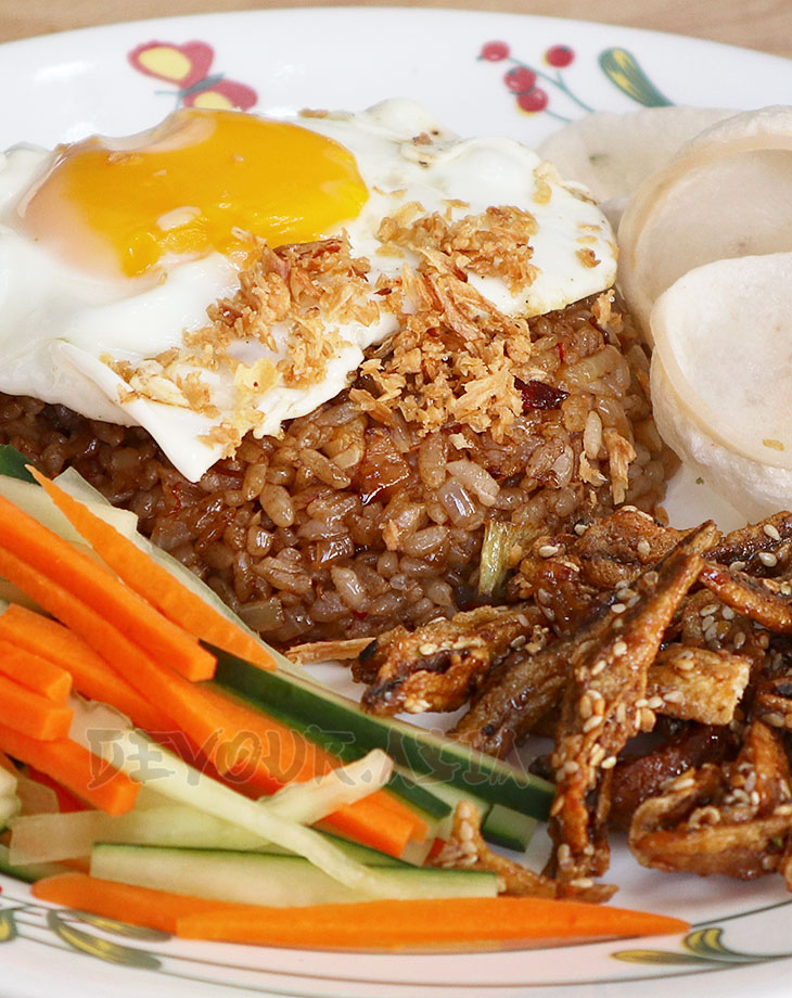 Nasi goreng (indonesian fried rice) with egg, carrot, cucumber, dilis and krupuk