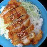 Chicken katsu drizzles with sauce and sesame seeds