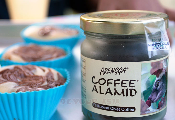 Civet coffee beans in a jar with cupcakes on the side