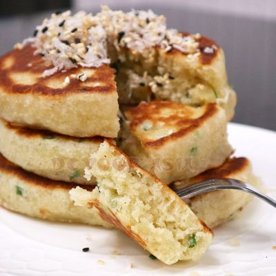 Stack of pancakes made with coconut milk and scallions topped with grated coconut and sesame seeds
