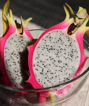 Cross cut of dragon fruit with magenta skin and white flesh