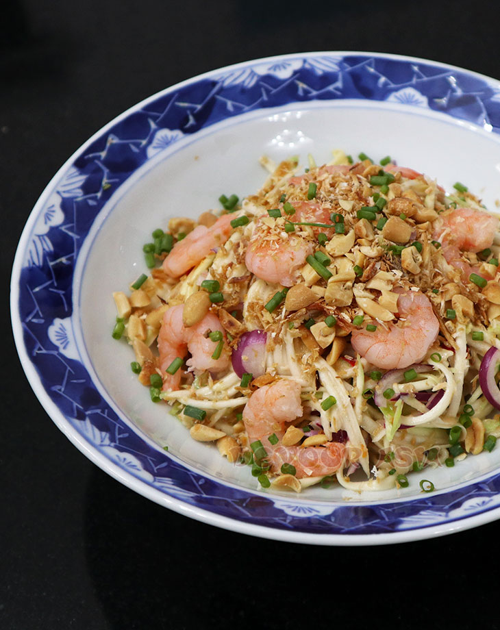 Yum Ma Muang (Thai green mango salad) with whole shrimps in a bowl