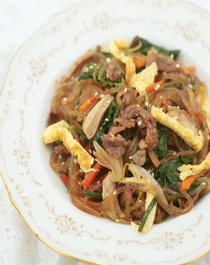 Top shot of japchae, Korean stir fried glass noodle dish, with beef, vegetables and egg in a bowl