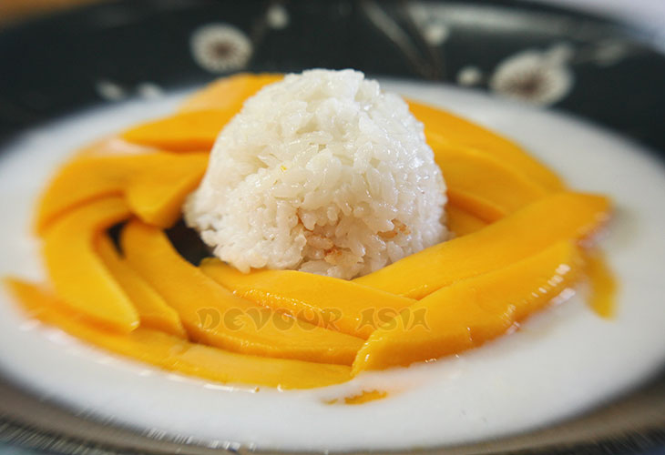 A scoop of sticky rice surrounded by slices of fresh ripe mango in a pool of coconut milk