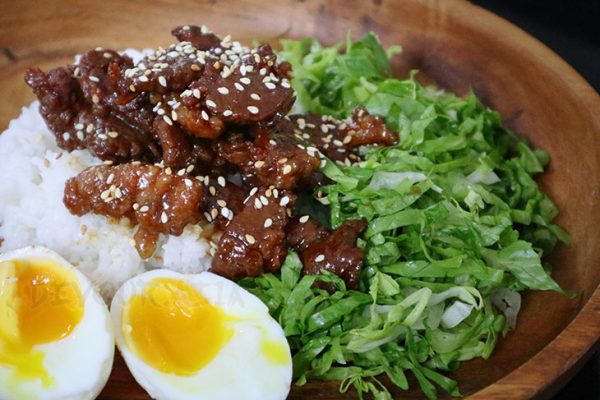 Beef shigureni topped with toasted sesame seeds, served with rice, lettuce and egg