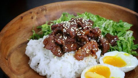 Beef shigureni over rice with shredded lettuce and egg on the side