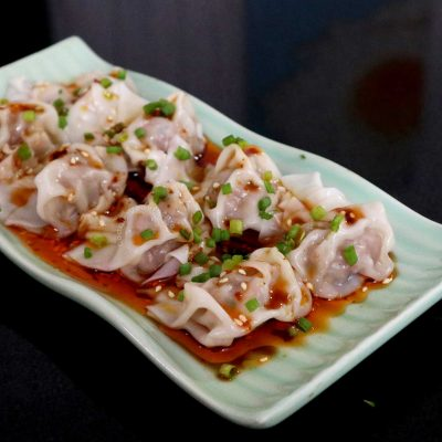 Wontons in Sichuan Chili Oil on Green Plate