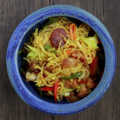 Singapore noodles (curry bee hoon) in blue stoneware bowl