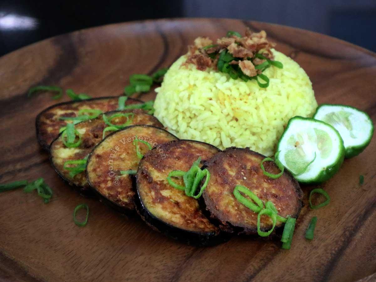 Garam masala eggplants with yellow rice and kaffir lime halves on acacia plate