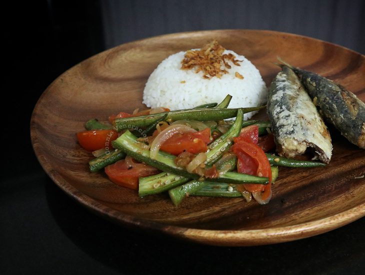 Sauteed orka and tomatoes with fried fish and rice on wooden plate